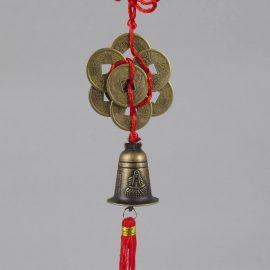 malý prívesok so zvonom šťastia a mincami